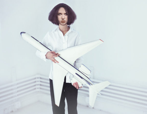 Young Woman Holding Large Model Airplane